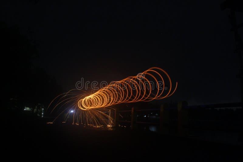 Steelwool gör fyrverkerier i midnatt arkivbilder
