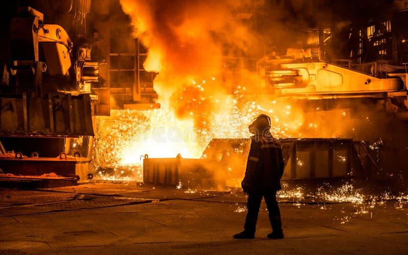 Steelworker nära en tryckvågpanna med gnistor royaltyfri bild