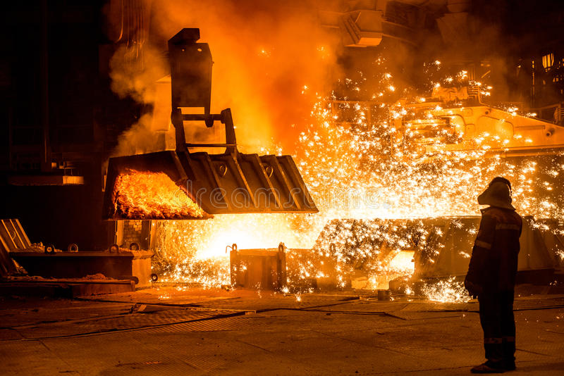 Steelworker near a blast furnace with sparks. Foundry royalty free stock photography