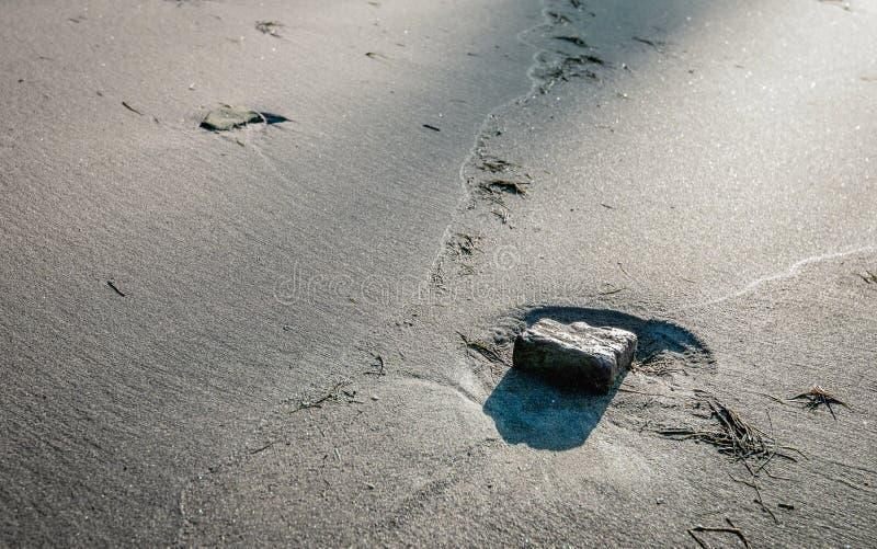 Steen in een kuiltje op het strand royalty-vrije stock afbeeldingen