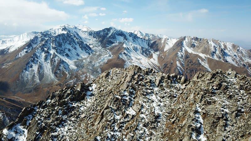 Steen en snow-capped bergen Blauwe hemel en wolken Het schieten met de hommel royalty-vrije stock foto