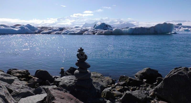 Steen met Drijvende Blauwe Ijsbergen op Blauw Meer en Bergenweergeven royalty-vrije stock afbeelding