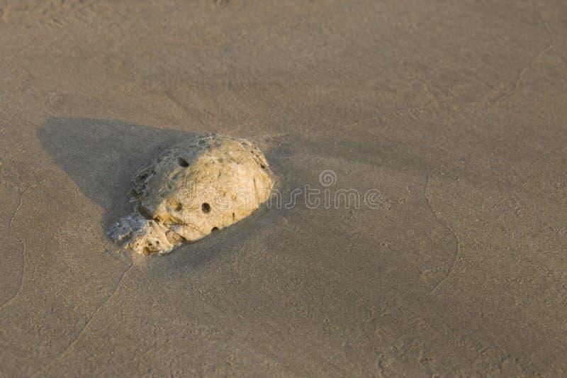 Steenabstractie in het zand op de kust stock foto