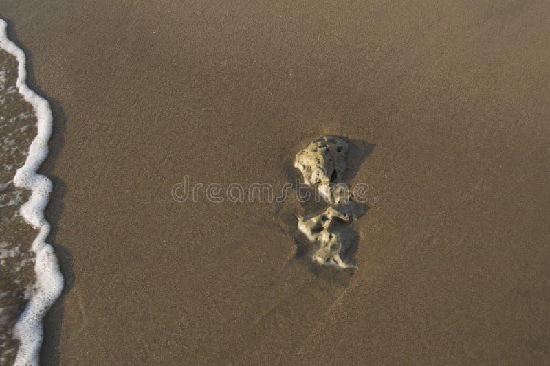 Steenabstractie in het zand op de kust stock foto's