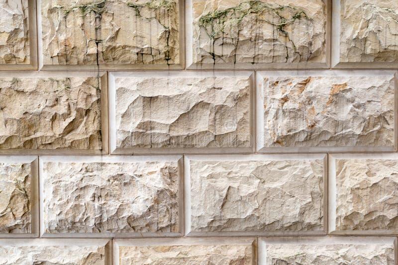 Steenachtergrond, het patroontextuur van de zandmuur Gele natuursteenvoorgevel, muurtegels stock afbeelding
