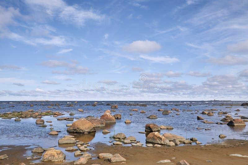 Steenachtig strand op een zonnige dag stock foto's