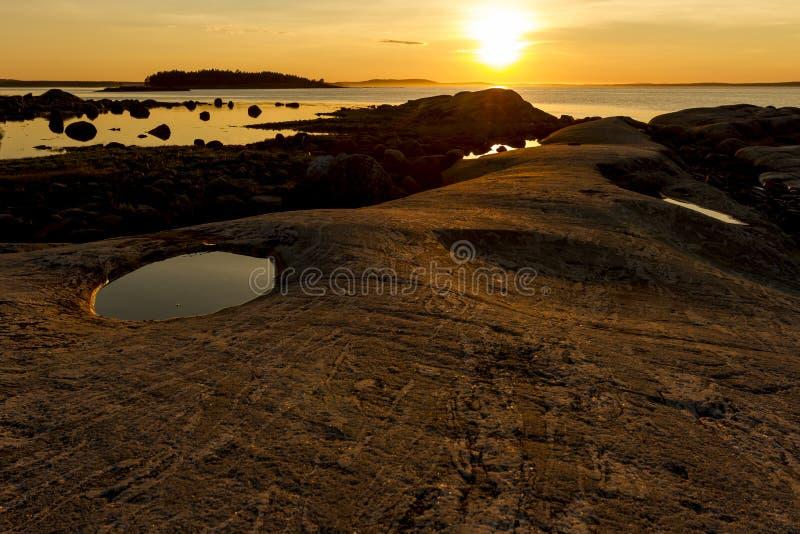 Steenachtige kustlijn, stille mooie gouden zonsondergang op het overzees De aardachtergrond van de zomer royalty-vrije stock foto's