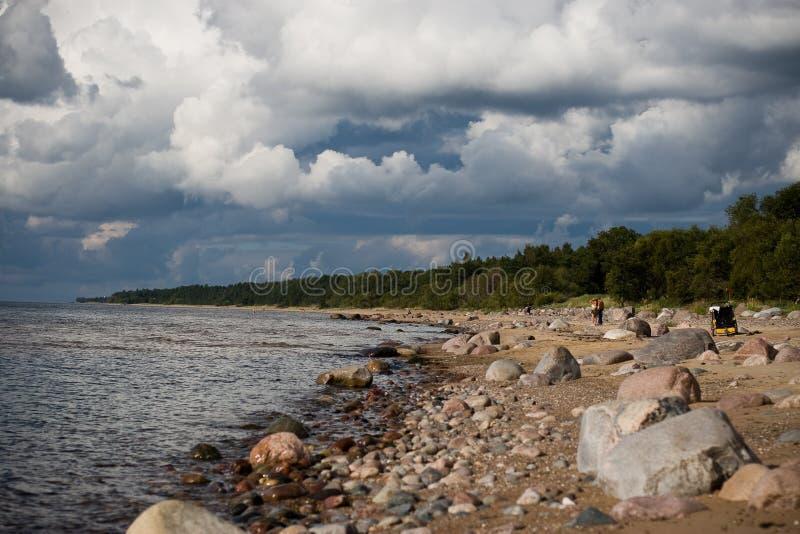 Steenachtige zeekust met onweerswolken stock foto's