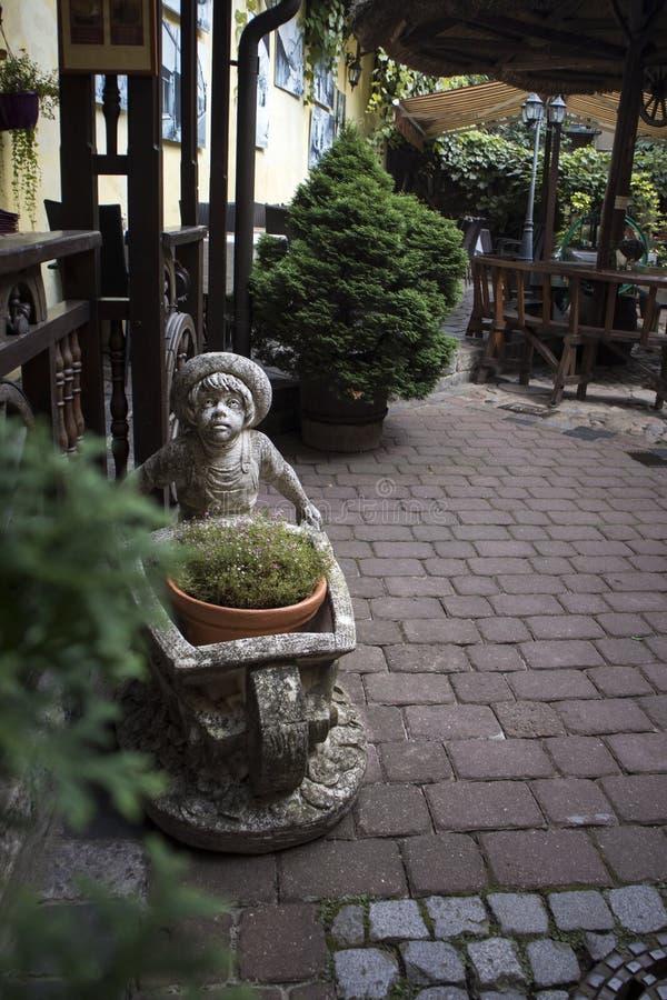 Steenbeeldhouwwerk van een jongen die een kar in de binnenplaats van een woningbouw draagt royalty-vrije stock afbeelding