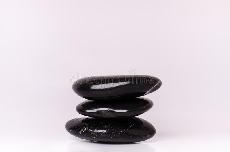 Steenbehandeling Zwarte die stenen op een witte achtergrond masseren Hete stenen saldo zen als concepten Basaltstenen stock afbeeldingen