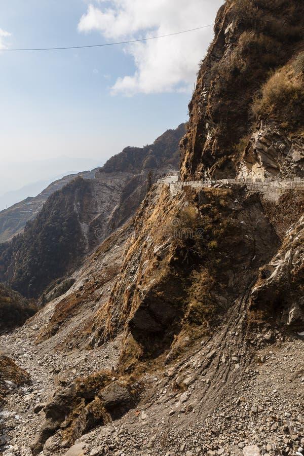 Steenberg met weg en achtergrond in berg en blauwe hemel in de winter dichtbij de manier aan Tsomgo-Meer in Gangtok Sikkim, India stock foto's
