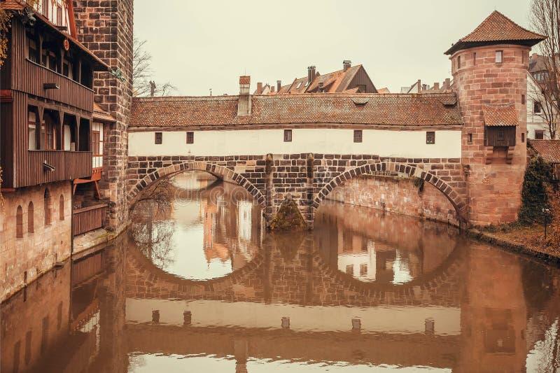 Steenbrug met baksteentoren en huizen over een kalme waterrivier binnen stad royalty-vrije stock afbeelding