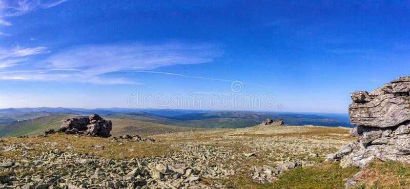 Steendagzomende aardlagen op een bergplateau Mooi panorama van de blauwe bewolkte hemel en de bergketens en valleien Noordelijke  royalty-vrije stock fotografie