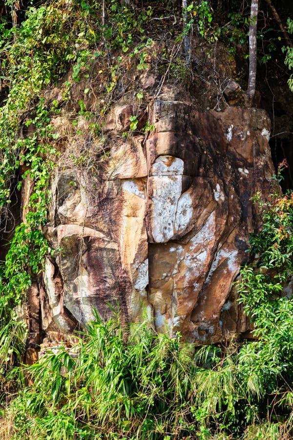 Steengezicht van Boedha door de Schilderachtige weg in bergen van Nationaal park Bokor die tot het Verlaten Paleis van hotelbokor stock foto's