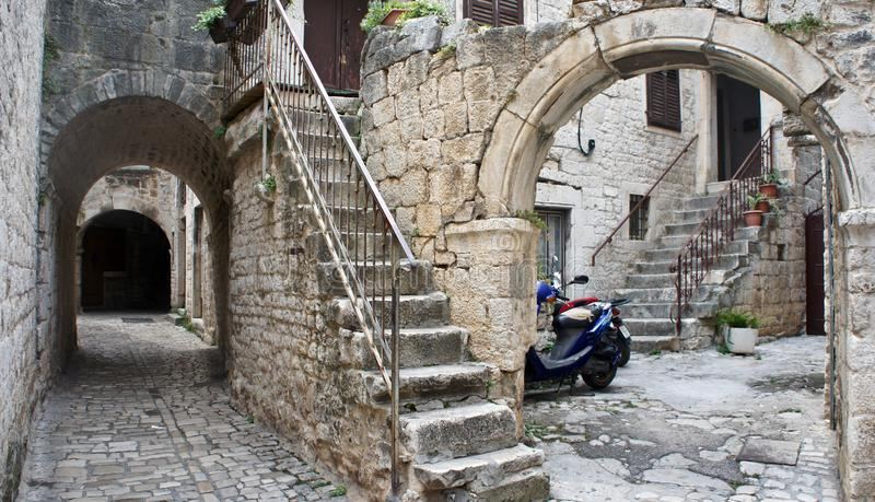 Steenhuizen in smalle straat van oude stad, mooie architectuur met archs en treden, Trogir, Dalmatië, Kroatië stock fotografie