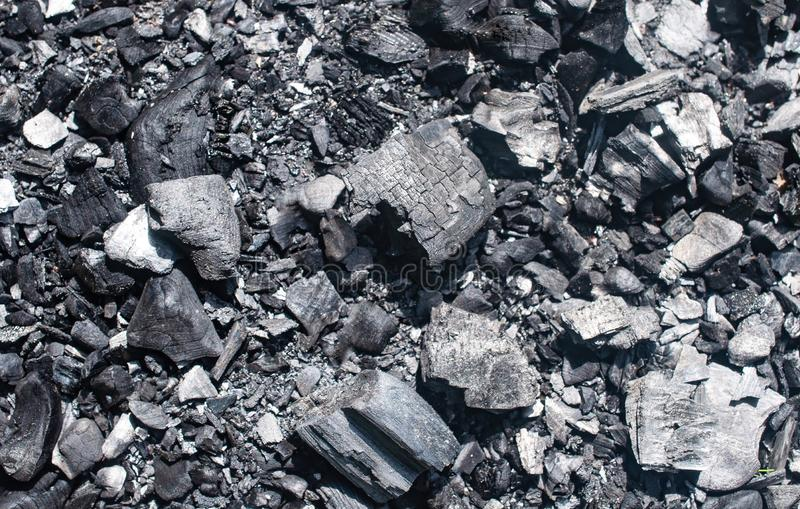 Steenkool en as van een brand op de bosachtergrond royalty-vrije stock afbeeldingen