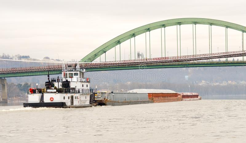 Steenkoolaak die onderaan de rivier van Ohio onder een brug gaan royalty-vrije stock afbeeldingen