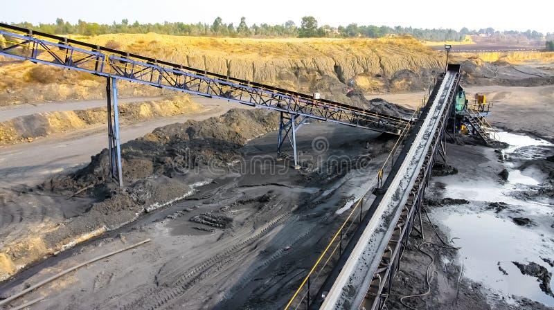 Steenkoolerts op een transportband voor verwerking stock fotografie
