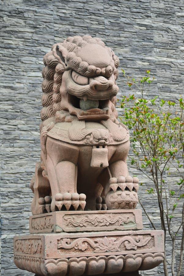 Steenleeuw die zich voor de Chinese stadsmuur bevinden stock afbeeldingen