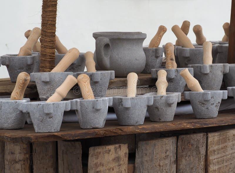 Steenmortier met houten stamper in een plank van een markt Een steenwaterkruik in het midden stock afbeeldingen