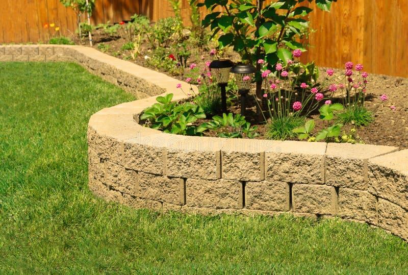 Steenmuur met het perfecte gras modelleren in tuin met kunstmatig gras royalty-vrije stock afbeelding