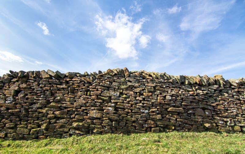 Steenmuur naast een grasrijk gebied in landelijk Engeland royalty-vrije stock afbeelding