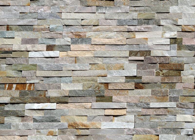Steenmuur van gestreepte gestapelde plakken van natuurlijke rotsen wordt gemaakt die Bekleding voor buitenkanten, stock fotografie
