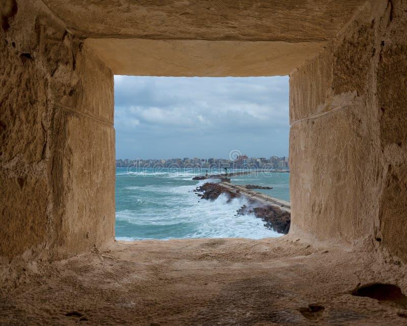 Steenraamkozijn die barrière en ingang van de oude haven van het oosten van de stad van Alexandrië overzien bij het Middellandse- royalty-vrije stock foto