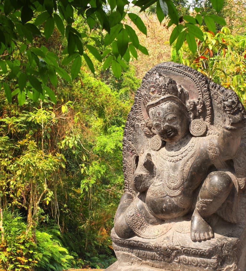 Steenstandbeeld van dansende Hindoese god en bomen in regenwoud royalty-vrije stock foto