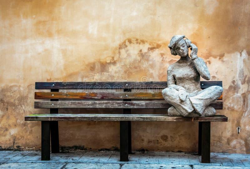 Steenstandbeeld van een kereltje die en aan muziek op een houten bank zitten luisteren royalty-vrije stock foto's