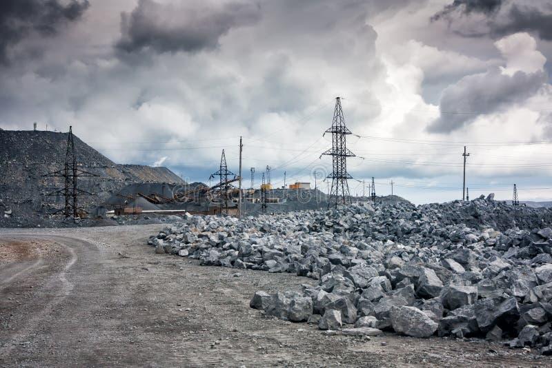 Steenstortplaatsen, machtslijnen en verpletterende machines in een steengroeve in bewolkt weer stock fotografie