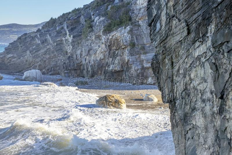 Steenstrand door klippen met tegemoetkomende schuimende golven wordt omringd die royalty-vrije stock afbeelding