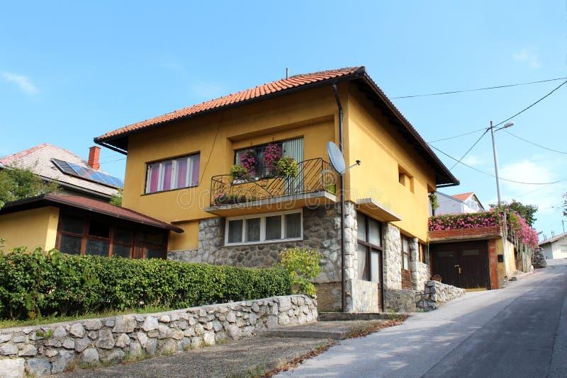 Steentegels en geel familiehuis in de voorsteden aan kant van kleine die heuvel met bloemen en haag naast bedekte weg wordt omrin stock afbeelding