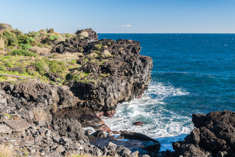 Steep black cliff in Catania, formed by ancient lava flows from volcano Etna royalty free stock photos