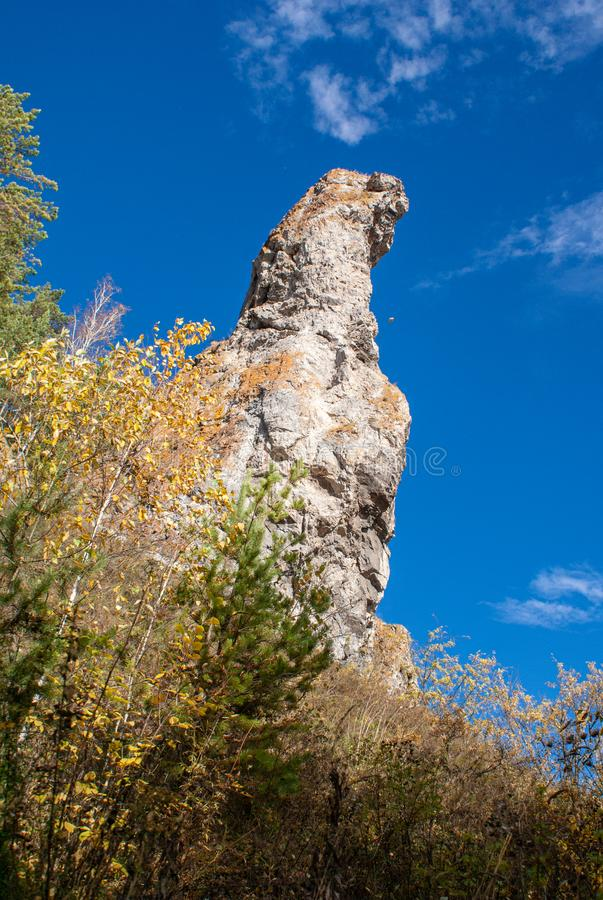Steep cliff against the blue sky. Close-up on a sunny autumn day. Steep cliff against the blue sky and trees. Close-up on a sunny autumn day royalty free stock image