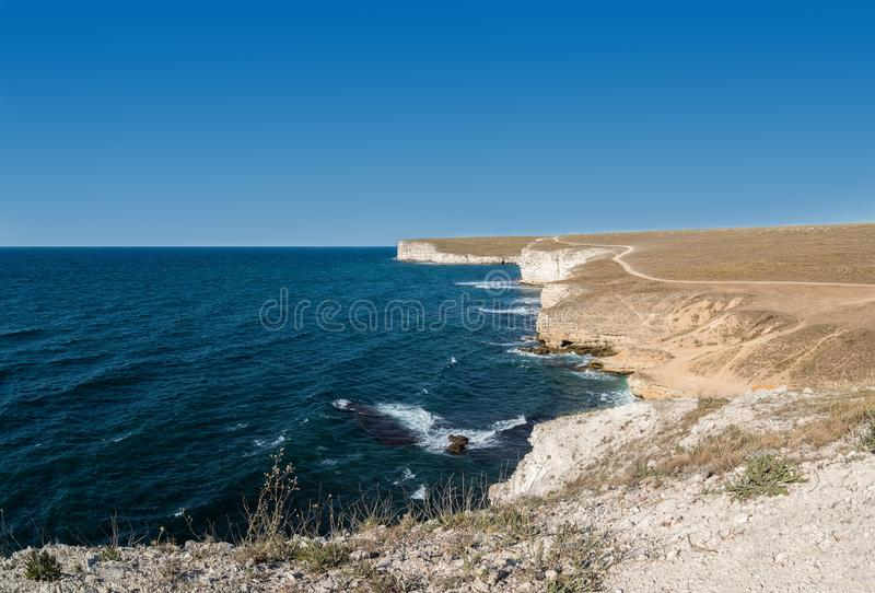 Steep cliff and azure water. Reflection of sunlight in the water stock image