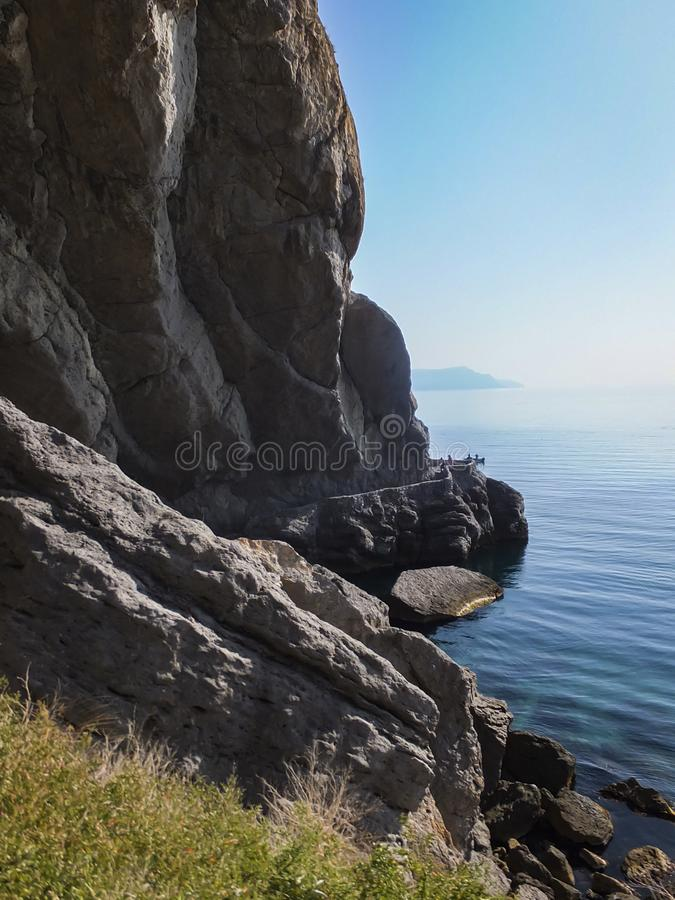 Steep cliff and huge stones on the shores of the blue water of the Black Sea. The coast of the village of Novy Svet in the Crimea. Golitsyn or Falcon trail royalty free stock photo