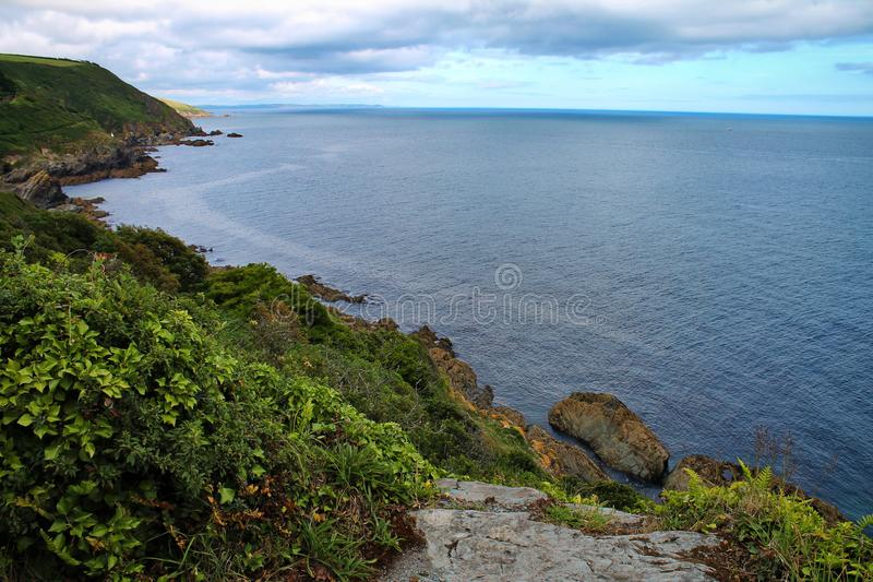 Looking down green cliffs towards a calm blue sea. Steep cliffs descend towards a calm, blue ocean. The cliffs are covered with green vegetation and the sky is royalty free stock images
