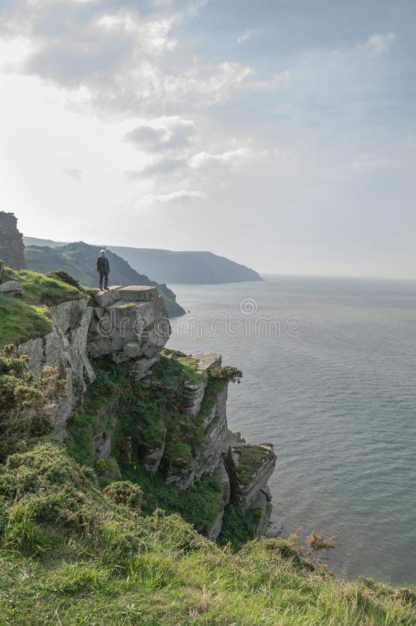 Steep cliffs with distant figure near the Valley of the Rocks ar stock image