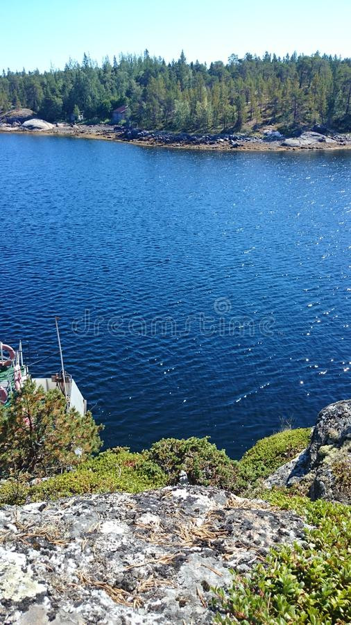 A steep coast over the rippling waters. Bright blue White Sea under the unexpectedly hot sun royalty free stock photos