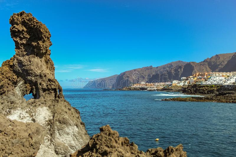 Steep high lava rock cliffs. Blue sea horizon, natural sky background royalty free stock images
