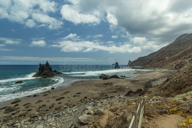 Steep high lava rock cliffs. Blue sea horizon, natural sky background stock photos