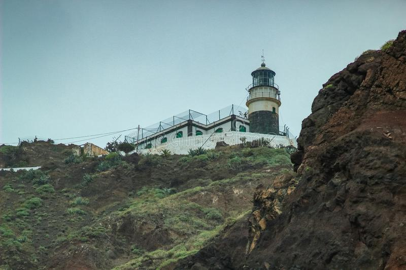 Steep high lava rock cliffs on on the east of Tenerife. Sea lighthouse, natural sky background stock photos