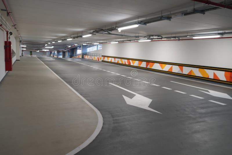 Steep paving descent to the parking lot. Brand new descending roads inside parking lot. Indoor parking lot exit passage stock image