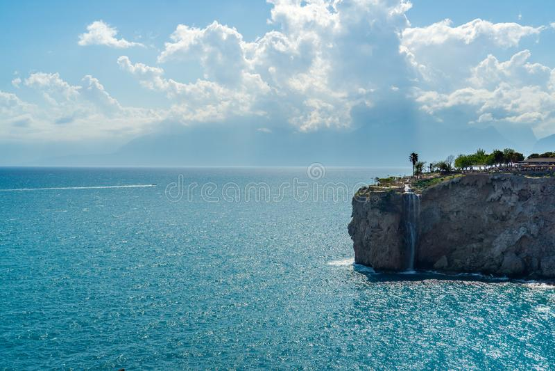Steep rocky beach with waterfall stock photo