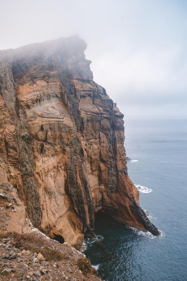 Steep rocky cliff. At Madeira Island by foggy morning stock images