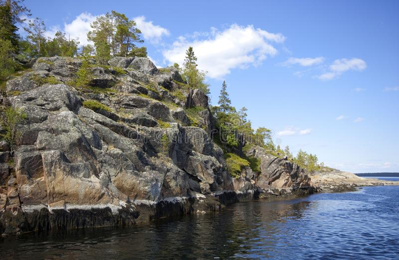 Steep rocky-kust van graniet-eiland in zonlicht, stock afbeeldingen