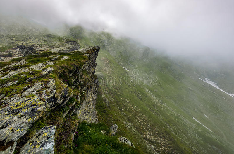 Steep slope on rocky hillside in fog. Edge of steep slope on rocky hillside in foggy weather. dramatic scenery in mountains stock photos