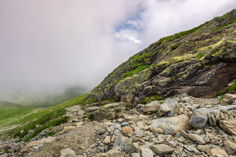 Steep slope on rocky hillside in fog. Edge of steep slope on rocky hillside in foggy weather. dramatic scenery in mountains stock photo