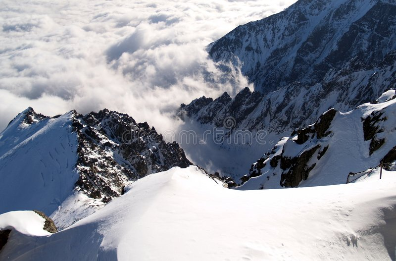 Steep snowy mountainside. Overlooking rugged snow-covered mountainside royalty free stock photo